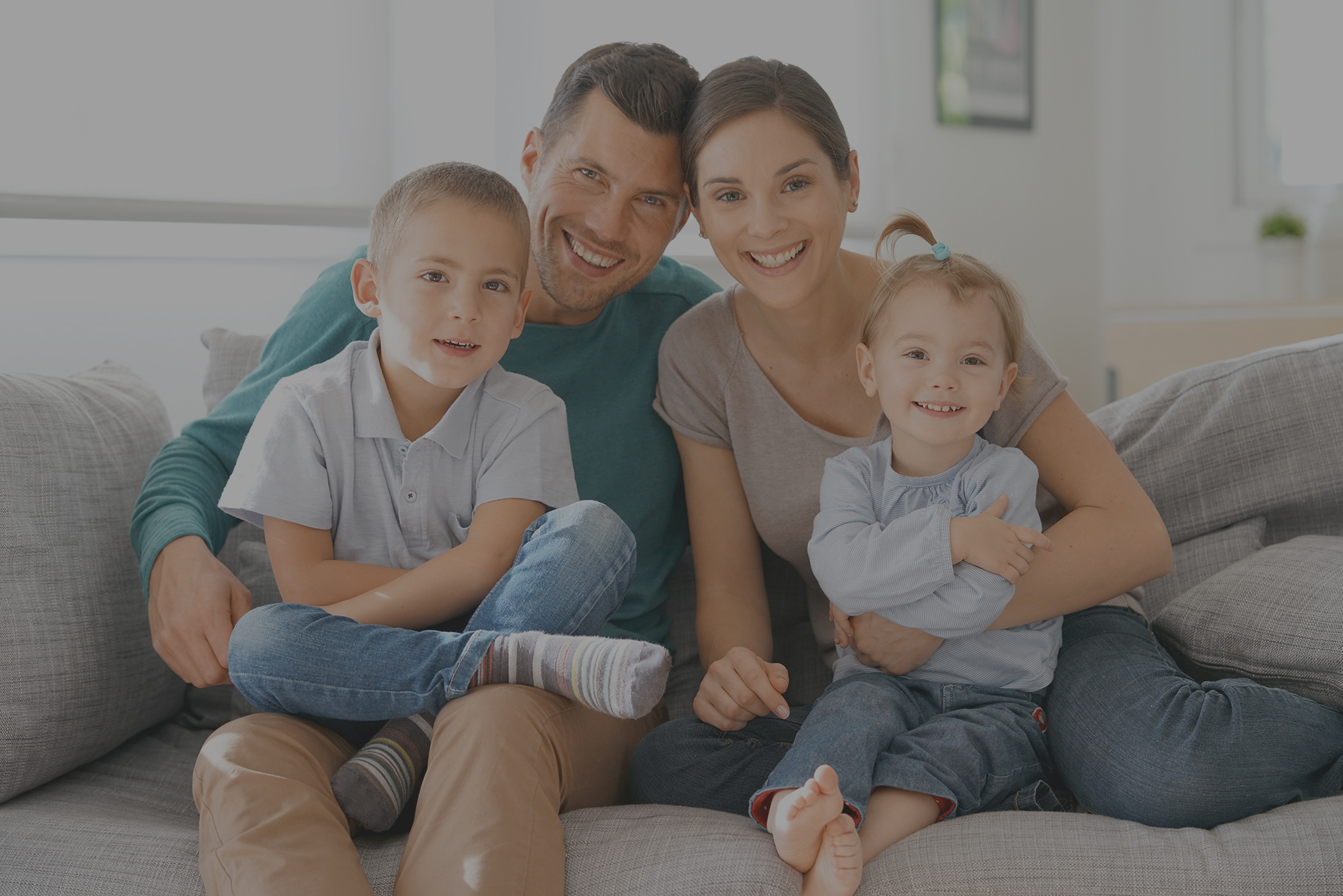 Happy family of four sitting on sofa